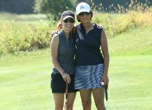Two female golfers arm in arm on a putting green