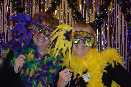Two women don masks at a Mardi Gras Bunko celebration