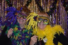 Two women don masks at a Mardi Gras Bunko celebration