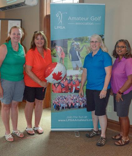 four women golfers with chapter banner