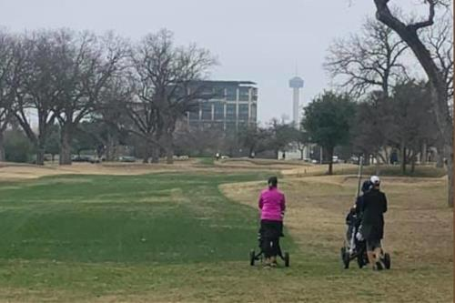 two women golfers pushing carts on Brackenridge Golf Course with Tower of the Americas in the background